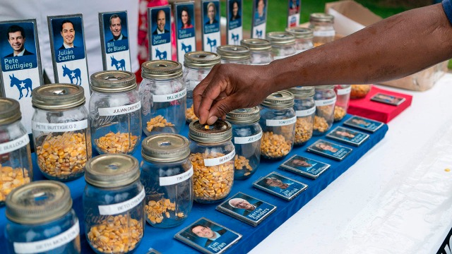"""A photo of people put kernels into jars representing presidential candidates in a """"corn poll"""" at the the Iowa State Fair on Aug. 11. (Alex Edelman/AFP/Getty Images)"""